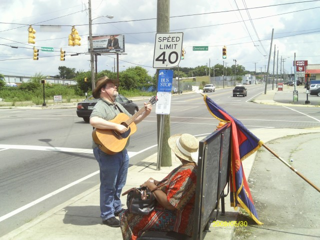 Singing a prophetic song to a woman on a bus stop bench.